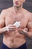 Przystojny dysponowany facet stosuje moisturizer dla twarzy Zdjęcie Royalty Free