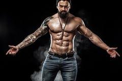 Przystojny dysponowany mężczyzna pozuje być ubranym w cajgach z tatuażem Bawi się pojęcie odizolowywającego na czarnym tle i faso obrazy royalty free