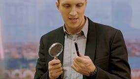 Przystojny ekspert sprawdza pióro z magnifier obiektywem w kostiumu, handheld strzał zdjęcie wideo