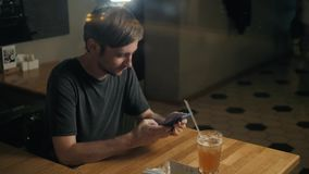 Przystojny elegancki mężczyzna opuszcza wiadomość w kawiarnia prętowym pije koktajlu używać głosu rozpoznanie, mówi przy smartpho zbiory