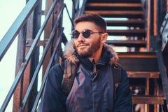 Przystojny elegancki młodego człowieka obsiadanie na schodkach outside zdjęcia stock