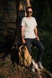 Przystojny elegancki młody człowiek jest ubranym białych okulary przeciwsłonecznych z plecakiem w jego ręce i koszulkę jest podró Obraz Royalty Free