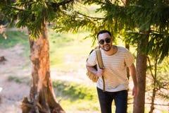 Przystojny elegancki młody człowiek jest ubranym białych okulary przeciwsłonecznych z plecakiem w jego ręce i koszulkę jest podró Fotografia Royalty Free