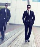 Przystojny elegancki mężczyzna w eleganckim czarnym kostiumu i okularach przeciwsłonecznych Fotografia Stock