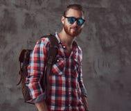 Przystojny elegancki rudzielec podróżnik w flanelowej koszula i okularach przeciwsłonecznych z plecakiem, pozuje w studiu na szar obrazy stock