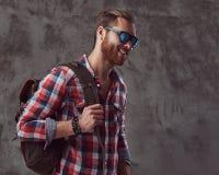 Przystojny elegancki rudzielec podróżnik w flanelowej koszula i okularach przeciwsłonecznych z plecakiem, pozuje w studiu na szar zdjęcie stock
