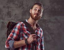 Przystojny elegancki rudzielec podróżnik w flanelowej koszula z plecakiem, pozuje w studiu na szarym tle obraz stock