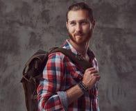 Przystojny elegancki rudzielec podróżnik w flanelowej koszula z plecakiem, pozuje w studiu na szarym tle obrazy royalty free