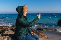 Przystojny facet bierze selfie na kamieniu blisko morza obraz stock