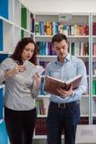 Przystojny facet i piękny rudzielec dziewczyny studiowanie w bibliotece Zdjęcie Stock