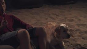 Przystojny facet jest odpoczynkowy z psem na plaży zbiory