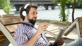 Przystojny facet jest siedzący czasopismo i trzymający Jest przyglądający ja i ono uśmiecha się Facet macha głowę w górę i na dół zdjęcie wideo