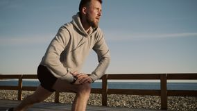 Przystojny facet rozciąga mięśnie nogi robi lunges blisko morza zbiory wideo