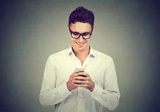 Przystojny facet używa ono uśmiecha się i smartphone zdjęcie royalty free