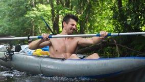 Przystojny facet w łodzi paddles wioślarstwo na rzecznym flisactwie _ Mężczyzna paddling wiosła w czółnie zdjęcie stock