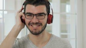 Przystojny facet w eyeglasses słucha muzykę w hełmofonach zdjęcie wideo