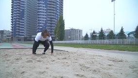 Przystojny facet w sportswear przyśpiesza i skoki w piasku przed kamera piaskiem rozpraszają spod cieków zbiory