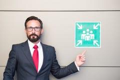 Przystojny fachowy lider wskazuje miejsce spotkania znak Mężczyzna ostrzega o miejscu spotkania w kostiumu i czerwonym krawacie obraz stock