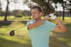 Przystojny golfisty mężczyzna bierze strzał fotografia stock