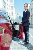 Przystojny grzeczny mężczyzna otwiera samochodowego drzwi Obraz Royalty Free