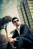 Przystojny i powabny młody człowiek siedzi outdoors z okularami przeciwsłonecznymi Zdjęcie Stock