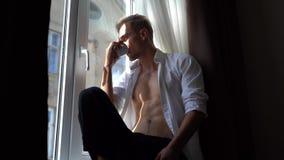 Przystojny i uwodzicielski młody człowiek z nagą półpostacią pije kawowego obsiadanie na windowsill w ranku zbiory