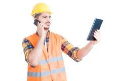 Przystojny inżynier opowiada na smartphone i używa pastylkę Obraz Stock