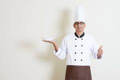 Przystojny Indiański męski szef kuchni trzyma talerza u w mundurze kciuka i Obrazy Royalty Free