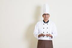 Przystojny Indiański męski szef kuchni trzyma talerza w mundurze Zdjęcia Royalty Free