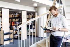 Przystojny inteligentny facet czyta książkę w bibliotece obraz stock