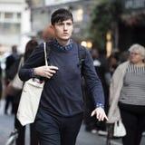 Przystojny jest ubranym pulower i torba chodzi ulicy Londyn Obraz Stock