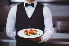 Przystojny kelner trzyma talerza Fotografia Royalty Free