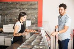 Przystojny klient wskazuje przy polewą dodawać w pizzy Obraz Royalty Free