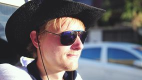 Przystojny kowboj podróżuje w furgonetce w słonecznym dniu w kapeluszu i okularach przeciwsłonecznych swobodny ruch 3840x2160 zdjęcie wideo