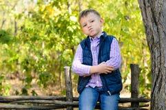 Przystojny Little Boy obsiadanie na Drewnianym ogrodzeniu Obraz Stock