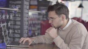Przystojny mężczyzny obsiadanie w cukiernianym lub w, czekać na jego rozkaz uważnie przy komputerem centrum i działaniu zbiory wideo