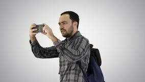 Przystojny młodego człowieka przewożenia plecak i brać obrazek on na gradientowym tle obraz stock