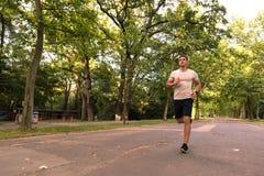 Przystojny młody człowiek jogging w parku fotografia stock
