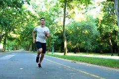 Przystojny młody człowiek jogging w parku fotografia royalty free