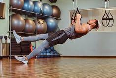 Przystojny mężczyzna ćwiczy z zawieszenie patkami w sprawność fizyczna klubie w sportswear fotografia stock