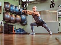 Przystojny mężczyzna ćwiczy z zawieszenie patkami w sprawność fizyczna klubie w sportswear zdjęcia stock