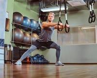 Przystojny mężczyzna ćwiczy z zawieszenie patkami w sprawność fizyczna klubie w sportswear fotografia royalty free