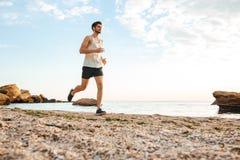Przystojny mężczyzna atlety bieg przy plażą Zdjęcie Royalty Free