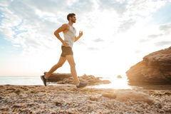 Przystojny mężczyzna atlety bieg przy plażą Obraz Royalty Free