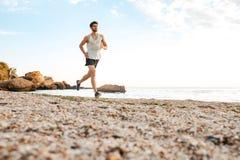 Przystojny mężczyzna atlety bieg przy plażą Zdjęcia Royalty Free