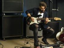 Przystojny mężczyzna bawić się gitarę elektryczną w studiu zdjęcia stock