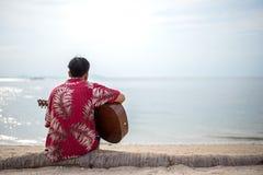 Przystojny mężczyzna bawić się klasycznego gitary obsiadanie na plaży w wakacjach Obrazy Royalty Free