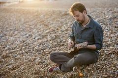 Przystojny mężczyzna bawić się ukulele zdjęcia royalty free