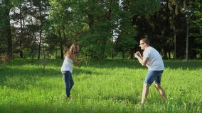 Przystojny mężczyzna bierze fotografie z kamerą młody szczęśliwy kobieta w ciąży w parku zdjęcie wideo