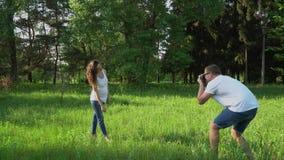 Przystojny mężczyzna bierze fotografie z kamerą młody szczęśliwy kobieta w ciąży w parku zbiory